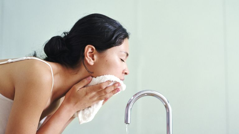 woman washing face with cloth over sink