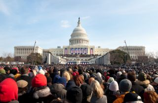A crowd of warmly dressed onlookers attends the 2009 inauguration of President Barack Obama.