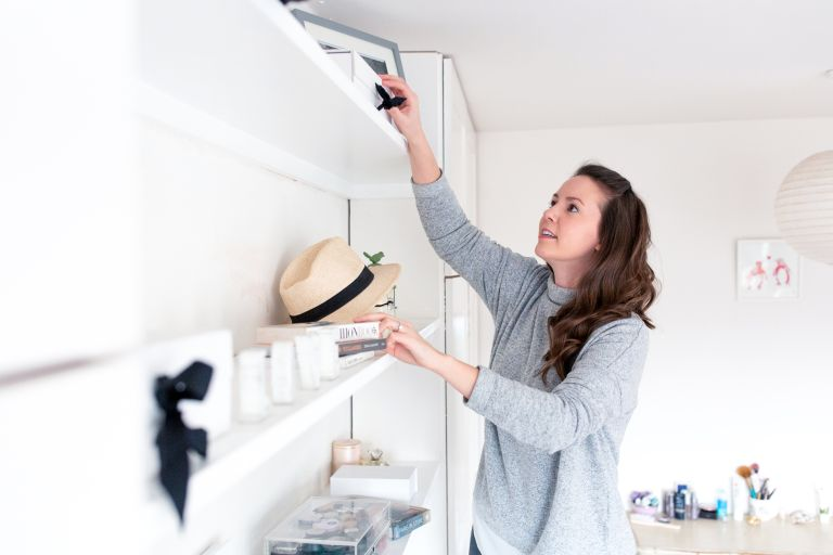 Lizzie Grant of Simplify Stuff cleaning shelves