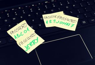Passwords written on Post-It notes on a laptop computer keyboard.