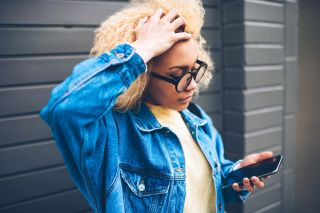 Young woman looking at phone and grasping hair in frustration.