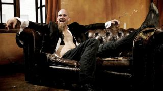 Nick Oliveri sprawled on an old sofa, holding a cigar and a glass of whiskey.