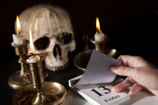 A skull and candles next to a calendar showing Friday the 13th.