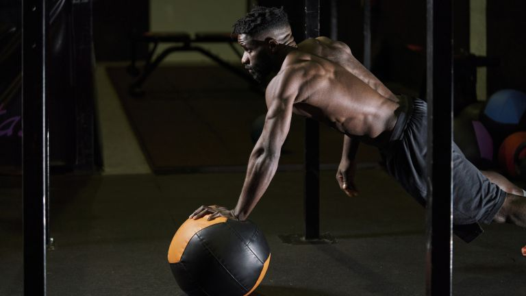 person working out on a medicine ball in a gym