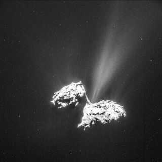 Comet hangs in starry space with bright jets of gas flying out