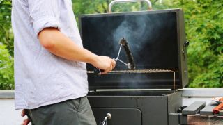 How to clean a barbecue grill: A man cleans a grill with a wire brush