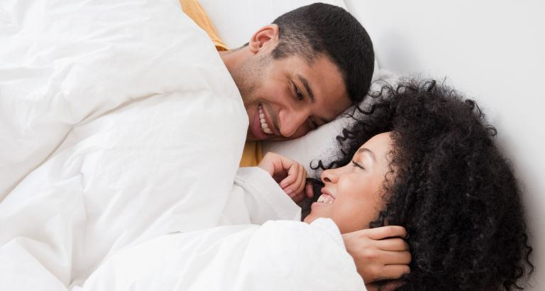 Young couple laying in bed and smiling