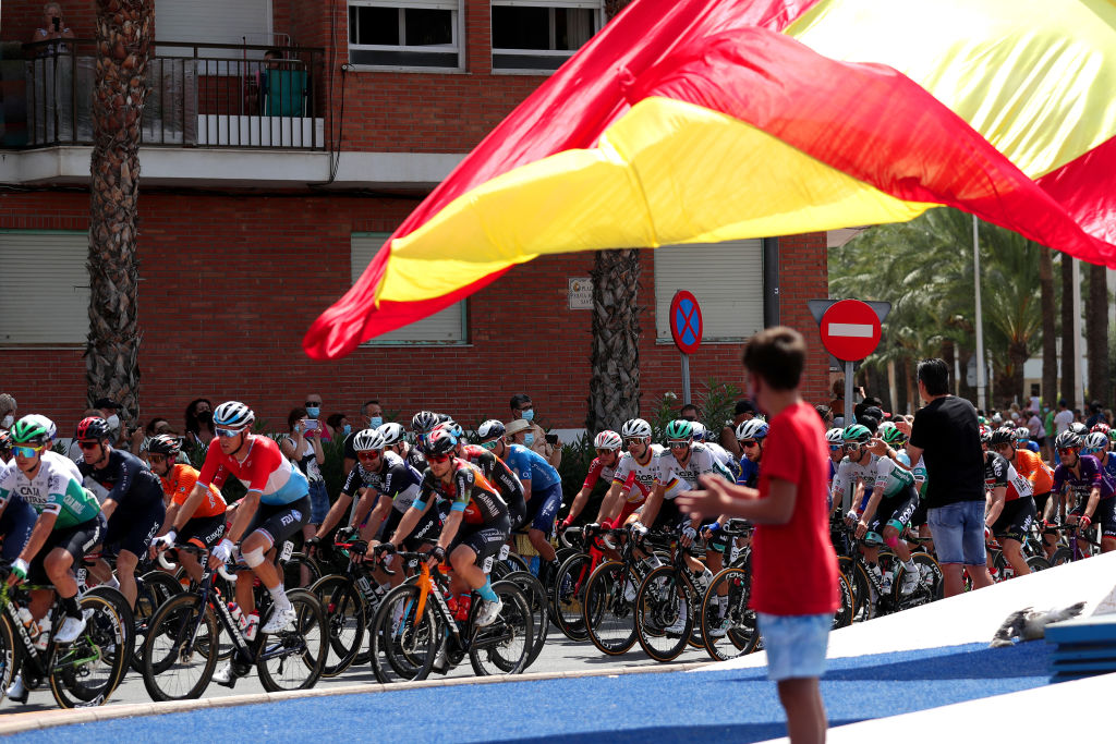 A Spanish flag waves in the breeze as the Vuelta a España goes past