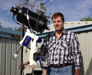 Amateur comet hunter Terry Lovejoy of Thornlands, Australia stands with the telescope and camera he used to discover the sungrazing comet C/2011 W3 (Lovejoy).