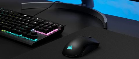 Corsair Sabre RGB Pro Wireless sitting on desk with keyboard