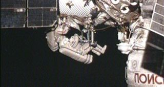 Spacewalker Dmitry Kondratyev installs the Molniya-Gamma experiment on the outside of the Zvezda service module. Oleg Skripochka (slightly out of frame) assists him.