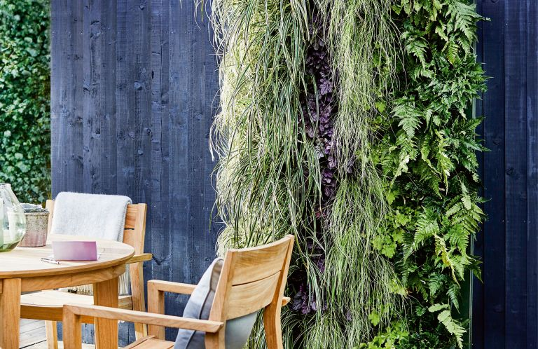 DIY vertical planters: an outdoor space with vertical gardening, plants growing up a black painted fence and an outdoor dining set