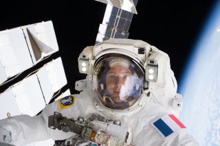 A person looks at the camera in a spacesuit, earth curving behind to his right.
