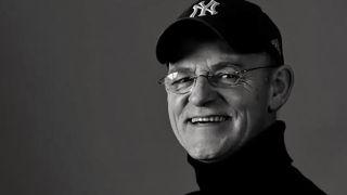 Black and white head shot portrait of Woody Woodmansy wearing a baseball cap