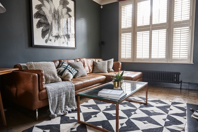 Jason Traves house: Living room with dark grey walls, tan leather sofa, minimalist coffee table with glass top, copper pendant light and black and white pattern rug over a wooden floor