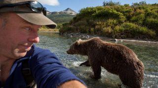 A photographer takes a selfie as a brown bear walks past.