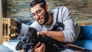 Man cuddling a dog on floor