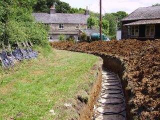 Installing a ground source heat pump ground array in slinkie trenches