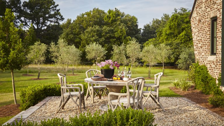 A set of nature-inspired garden chairs and table on a gravel dining area surrounded by trees