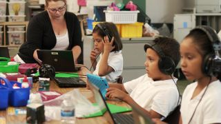 Kids use headphones and laptop computers in the classroom