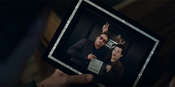Tony Stark holding a photo of himself and Peter Parker