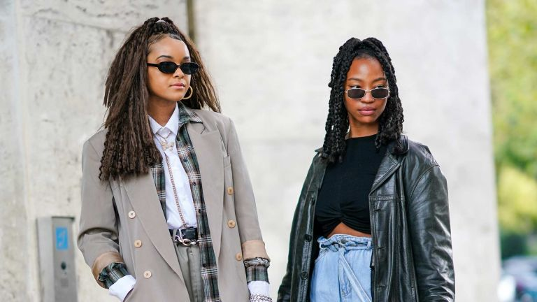 Two young women in 2000s fashion or y2k trends, like plaid, leather and rectangular sunglesses, are pictured during paris fashion week