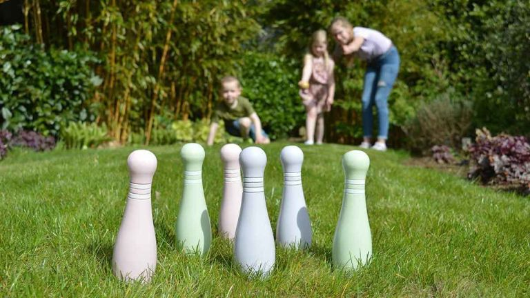 Traditional Garden Games Junior Wooden Skittles Set in garden on grass with children playing