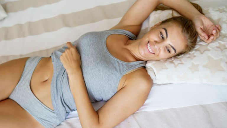 Smiling mature woman looking away while relaxing on bed - stock photo