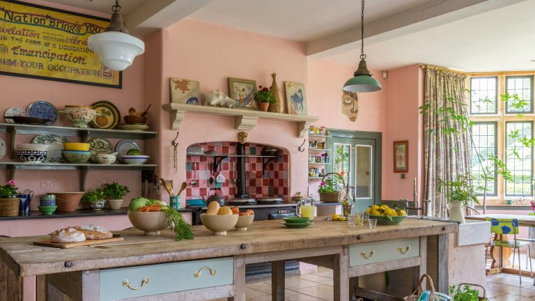 unfitted kitchen in manor house with antique cooks table, pink walls and Aga