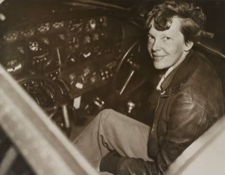 Amelia Earhart sitting in the cockpit of her Lockheed Electra airplane. In July 1937, Earhart and the plane were last seen on July 2, 1937 over the Pacific Ocean.