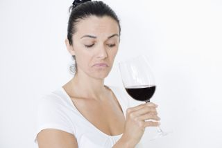 woman making a face and funny-smelling wine