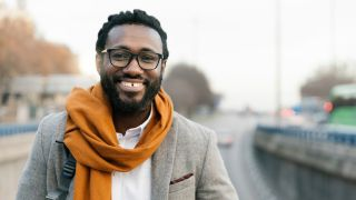 How should glasses fit your face: A man in a grey suit jacket and mustard scarf wears black frame glasses