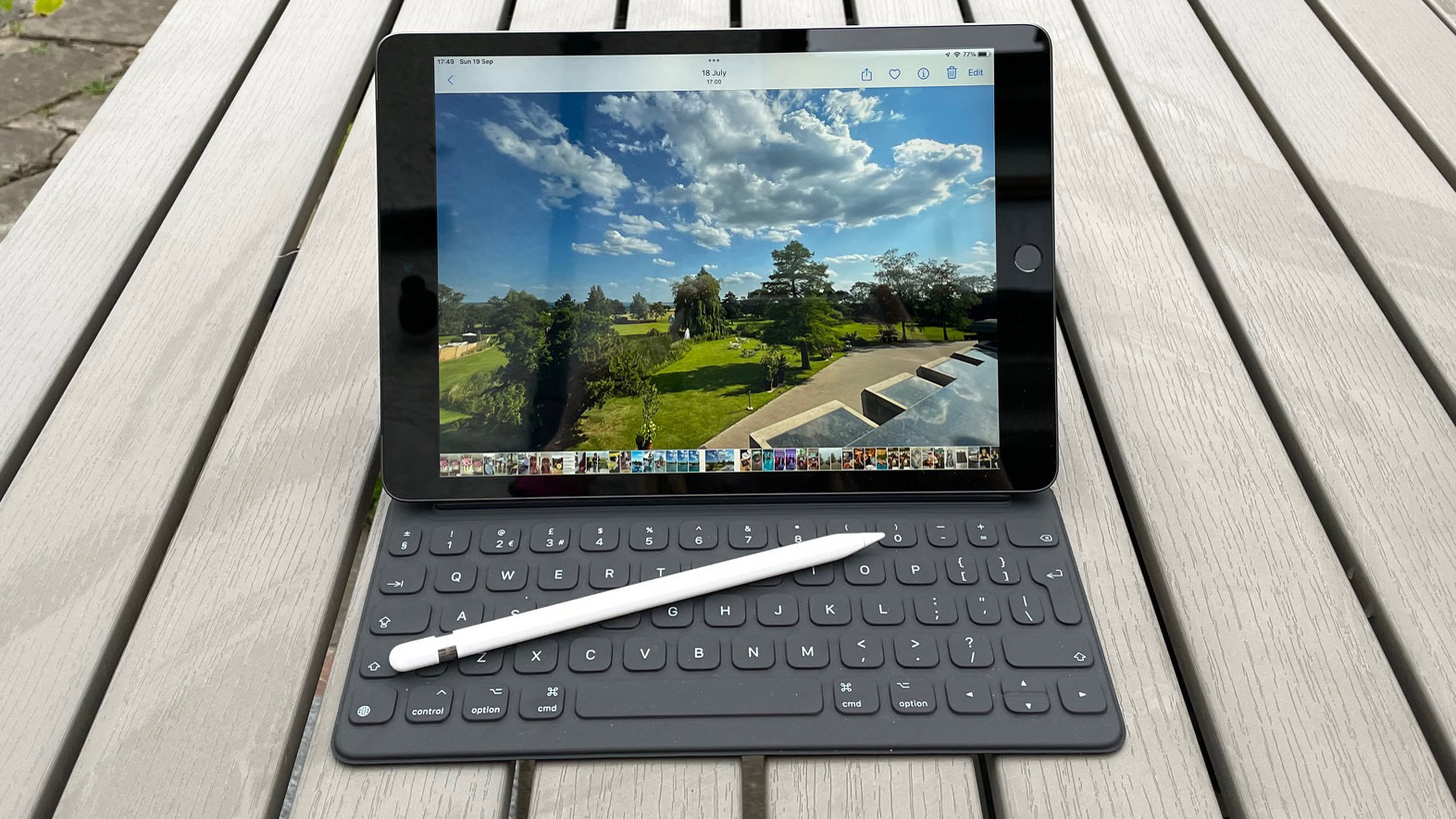 The Apple iPad 10.2 (2021) with the smart keyboard attached, with an Apple Pencil resting on the keyboard, outside