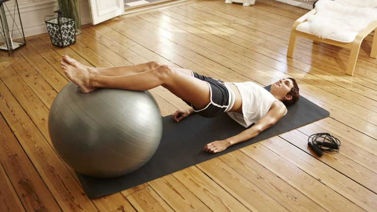 Woman working out her legs with a Swiss ball