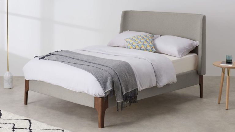 Made Roscoe King Size bed frame in beige colour styled in white bedroom with berber rug and marble floor lamp