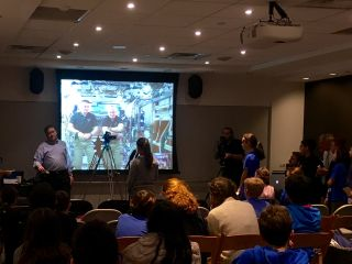 Students sit in a conference room talking to astronauts on the International Space Station, projected onto a screen.