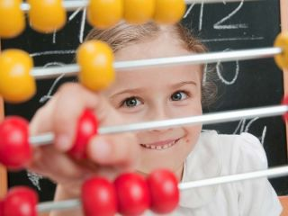 A young girl plays with an abacus in math class.