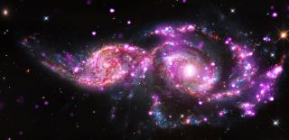This composite image of the grazing galaxies NGC 2207 and IC 2163 contains data from NASA's Chandra, Hubble and Spitzer space telescopes. (Chandra data shows up as pink, Hubble data as red, green and blue, and Spitzer data as red.)