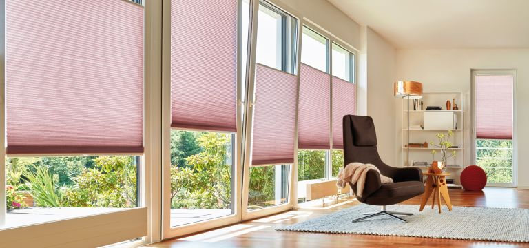 Pink blinds at patio doors in a living room. By Duette