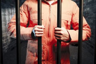 orange-jumpsuit-wearing prisoner grips bars of cell
