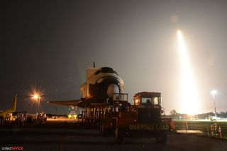 SpaceX Falcon 9 rocket launches over space shuttle mockup.