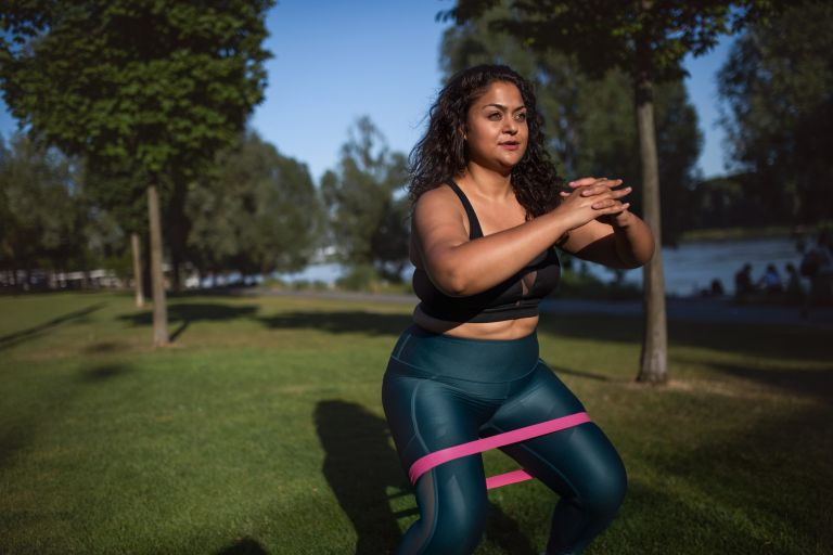 Mixed-race woman with elastic band doing sport in city, Proworks Glute Band