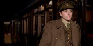 Jack Lowden boarding a train in uniform in Benediciton.