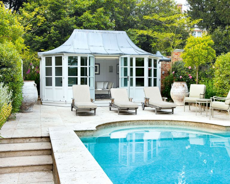 An example of pool area ideas showing a pool with sun loungers and chairs in front of a pool house retreat