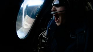 """Virgin Galactic's first test passenger Beth Moses looks out the window of the VSS Unity during a test flight with pilots Dave Mackay and Michael """"Sooch"""" Masucci, on Feb. 22, 2018."""