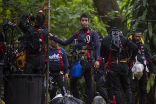 Thai divers carry supplies as rescue operations continue for 12 boys and their coach trapped at Tham Luang cave on July 5, 2018.