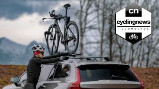 Cyclist fitting a time trial bike to the roof of a car using one of the best bike racks