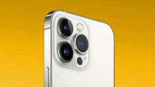 An image of the apple 13 pro max showing the camera module. The top half of the phone is pictured, against a yellow background