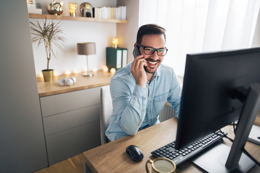 Smiling man on phone in home office