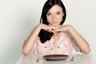 A woman sits with an empty plate in front of her